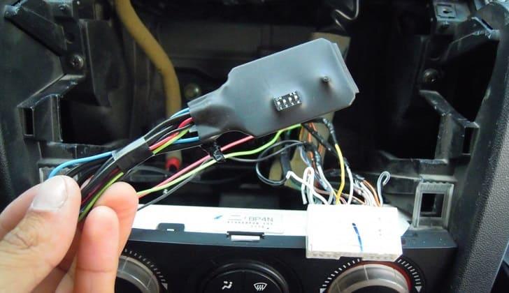 Снимают магнитолу для подключения адаптера